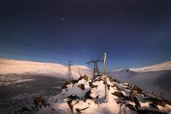 Supporto della linea ad alta tensione Un paesaggio della montagna di notte di inverno Fotografie Stock