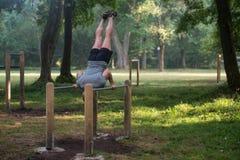 Supporto della mano sulle parallele simmetriche in parco all'aperto Immagini Stock Libere da Diritti
