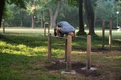 Supporto della mano sulle parallele simmetriche in parco all'aperto Immagine Stock