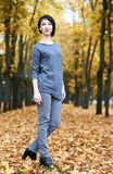 Supporto della ragazza nel parco con gli alberi gialli, stagione di autunno di caduta Fotografie Stock