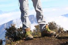 Supporto delle gambe della viandante sulla montagna Fotografia Stock