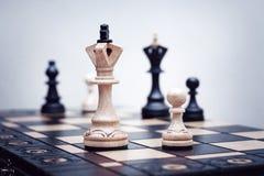 Supporto di parecchi pezzi degli scacchi su una scacchiera di legno fotografie stock