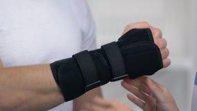Supporto di polso d'uso ortopedico femminile al paziente maschio, trattamento di trauma stock footage