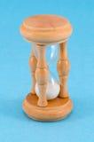 Supporto di vetro dell'orologio della sabbia di legno su fondo blu Fotografie Stock Libere da Diritti