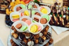 Supporto di vetro in pieno dei dolci e dei maccheroni differenti Fotografie Stock