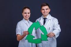 Supporto due, sorriso e tenuta felici in mani un segno, tre frecce verdi giranti Immagini Stock