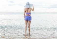 Supporto felice della donna del ritratto munito di casco sulla sabbia che guarda al mare Fotografie Stock