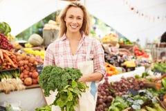 Supporto femminile della stalla al mercato dell'alimento fresco degli agricoltori fotografie stock libere da diritti