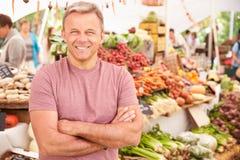 Supporto maschio della stalla al mercato dell'alimento fresco degli agricoltori Fotografie Stock