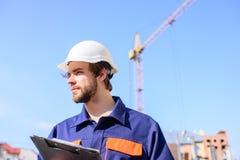 Supporto protettivo del casco dell'ingegnere davanti al fondo del cielo blu Il casco dell'ingegnere del costruttore funziona al c fotografia stock