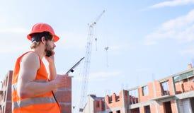 Supporto protettivo del casco del tipo davanti a costruzione fatta dai mattoni rossi Controlli il processo della costruzione Aran fotografia stock libera da diritti