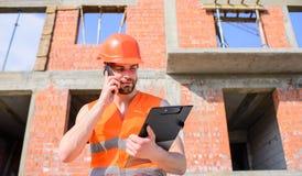 Supporto protettivo del casco del tipo davanti a costruzione fatta dai mattoni rossi La maglia ed il casco del costruttore funzio fotografia stock
