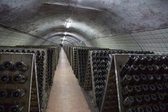 Supports avec des bouteilles de vin mousseux dans le sous-sol dans un établissement vinicole image stock