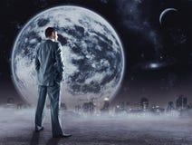 Supports d'homme d'affaires regardant la lune image stock