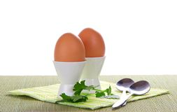 Supports with eggs, spoons and the striped napkin Stock Photos