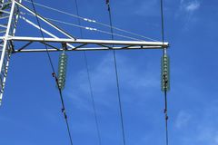 Supports high-voltage power lines against the blue sky with clou royalty free stock photography