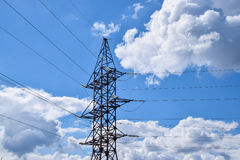 Supports high-voltage power lines against the blue sky with clouds. Electrical industry Royalty Free Stock Photography
