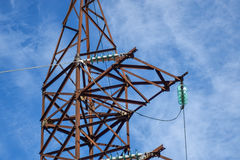 Supports high-voltage power lines against the blue sky with clouds. Electrical industry Stock Photos