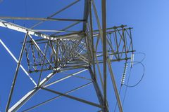 Supports high-voltage power lines against the blue sky. View fro royalty free stock image