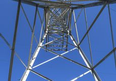 Supports high-voltage power lines against the blue sky. View fro royalty free stock photo