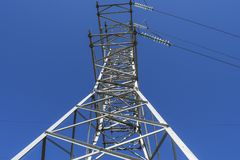 Supports high-voltage power lines against the blue sky. View fro stock photography