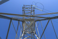 Supports high-voltage power lines against the blue sky. View fro royalty free stock images
