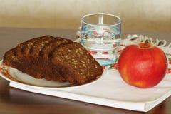 Supports sur la table une pomme rouge, l'eau dans un verre, pain horizo photographie stock