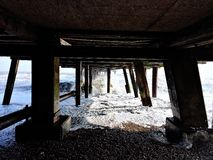 Supports under the pier at Southwold on a cold winter day. Underneath the pier Royalty Free Stock Photo