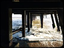 Supports under the pier at Southwold on a cold winter day. Underneath the pier Stock Image