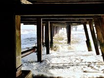 Supports under the pier at Southwold on a cold winter day. Underneath the pier Royalty Free Stock Image
