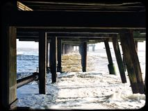 Supports under the pier at Southwold on a cold winter day. Underneath the pier Royalty Free Stock Photography