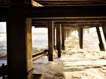 Supports under the pier at Southwold on a cold winter day. Underneath the pier Royalty Free Stock Images