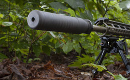 Suppressed fire. Modern sporting rifle with a silencer in the bushes Stock Photos
