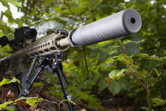 Suppressed rifle. Modern semi automatic rifle that has a silencer attached in the trees Royalty Free Stock Image