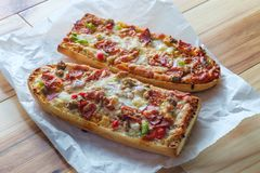 Supreme French Bread Pizza. With pepperoni sausage black olives red onion and green bell pepper toppings stock photo