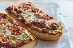 Supreme French Bread Pizza. With pepperoni sausage black olives red onion and green bell pepper toppings stock photography