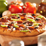 Supreme italian pizza with pepperoni and toppings. Close up photo of a supreme italian pizza with pepperoni and toppings shot with selective focus royalty free stock image