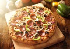 Supreme italian pizza with pepperoni and toppings. Photo of a supreme italian pizza with pepperoni and toppings royalty free stock photography