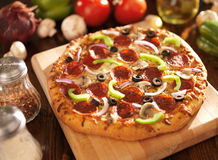 Supreme italian pizza with pepperoni and toppings. Photo of a supreme italian pizza with pepperoni and toppings shot with selective focus stock photography