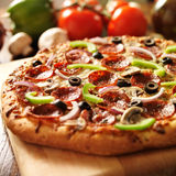 Supreme italian pizza with pepperoni and toppings. Photo shot with selective focus of a supreme italian pizza with pepperoni and toppings royalty free stock photo