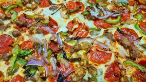 Supreme pizza close up with toppings. Close up color image of a supreme pizza with focus on the different variety of pizza toppings royalty free stock photography