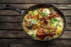 Supremes crémeux de fellets de poulet en sauce aux champignons avec le persil dans la poêle rustique de fonte photographie stock libre de droits