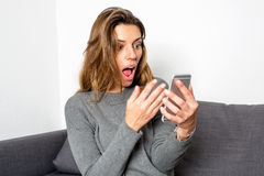 Suprise while looking on phone. Woman suprised while looking on smartphone Royalty Free Stock Image