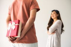 Suprise valentine gift from boyfriend. Beautiful Asian women looking at her men and smiling while boyfriend holding surprise valentine gift box behind with copy Royalty Free Stock Photo