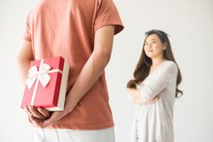 Suprise valentine gift to Asian girlfriend. Boyfriend hold and hide surprise valentine gift box to his beauty Chinese Asian girlfriend with copy space for text stock photo