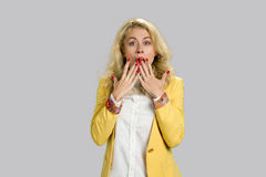 Suprised astonished young blonde woman. Shocked and surprised young blonde woman in formal wear covering her mouth with two hands, grey background Stock Photography