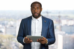 Suprised businessman with computer tablet. Sad black manager hold digital tablet on blurred background. Business owner in bewilderment with pc tablet in hands Royalty Free Stock Photography
