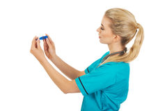 Suprised female nurse or doctor looking for thermometer Royalty Free Stock Photo
