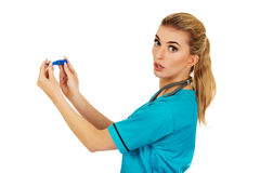 Suprised female nurse or doctor looking for thermometer Stock Image