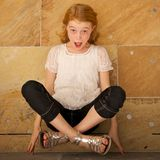 Suprised Girl Lifts Herself Up by Her Fingertips Stock Images